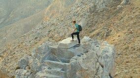 Τουρίστας που στέκεται στον υψηλό βράχο και που απολαμβάνει το επίτευγμά του που εξετάζει να περιβάλει απόθεμα βίντεο