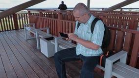 Τουρίστας που χρησιμοποιεί την ταμπλέτα στον πύργο άποψης φιλμ μικρού μήκους