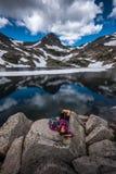 Τουρίστας στα υπόλοιπα κοριτσιών οδοιπόρων του Κολοράντο στην μπλε λίμνη Στοκ Φωτογραφίες