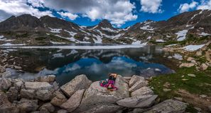 Τουρίστας στα υπόλοιπα κοριτσιών οδοιπόρων του Κολοράντο στην μπλε λίμνη Στοκ Φωτογραφία