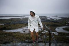 Τουρίστας στους άσπρους περιπάτους αδιάβροχων στην ακτή της Ισλανδίας στοκ εικόνες με δικαίωμα ελεύθερης χρήσης