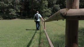 Τουρίστας στο λιβάδι κοντά στον ξύλινο φράκτη απόθεμα βίντεο