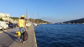 Τουρίστας όμορφος, brunette νέων κοριτσιών στα γυαλιά ηλίου σε μια κίτρινη μπλούζα, τζιν παντελόνι, ένα κίτρινο καπέλο και με χρω φιλμ μικρού μήκους