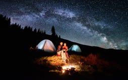 Τουρίστες ζεύγους κοντά στην πυρά προσκόπων και σκηνές κάτω από το σύνολο νυχτερινού ουρανού των αστεριών και του γαλακτώδους τρό Στοκ Εικόνες