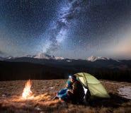 Τουρίστες ζεύγους που απολαμβάνουν στη στρατοπέδευση τη νύχτα, έχοντας ένα υπόλοιπο κάτω από το όμορφο σύνολο νυχτερινού ουρανού  στοκ φωτογραφία με δικαίωμα ελεύθερης χρήσης