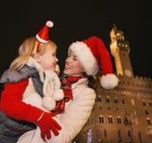 Τουρίστες μητέρων και παιδιών στα καπέλα Χριστουγέννων που αγκαλιάζουν στη Φλωρεντία Στοκ Φωτογραφία