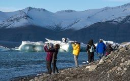 Τουρίστες που επισκέπτονται τη λιμνοθάλασσα παγετώνων Jokulsarlon στην Ισλανδία στοκ εικόνα