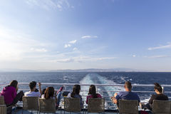 Τουρίστες που κάθονται στο κατάστρωμα ενός τίτλου πλοίων στο isla Santorini Στοκ φωτογραφία με δικαίωμα ελεύθερης χρήσης