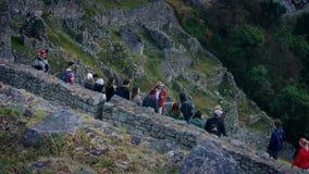 Τουρίστες που κοιτάζουν γύρω από τις αρχαίες καταστροφές στη βουνοπλαγιά απόθεμα βίντεο