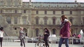 Τουρίστες που περπατούν κοντά στο παλάτι του Λούβρου πυραμίδων γυαλιού απόθεμα βίντεο