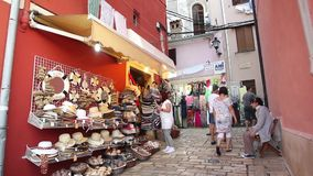 Τουρίστες που περπατούν μπροστά από το κατάστημα θερινών καπέλων απόθεμα βίντεο