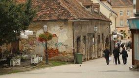 Τουρίστες που περπατούν στην όμορφη παλαιά οδό με τα κόκκινα κτήρια στεγών, πόλη του Ζάγκρεμπ φιλμ μικρού μήκους