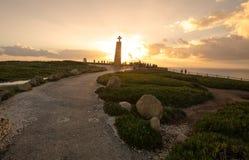 Τουρίστες που προσέχουν το ηλιοβασίλεμα κοντά στο διαγώνιο μνημείο σε Cabo DA Στοκ Εικόνα