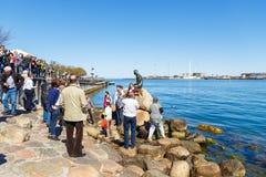 Τουρίστες που προσέχουν το μικρό άγαλμα χαλκού γοργόνων μια γοργόνα στοκ φωτογραφία με δικαίωμα ελεύθερης χρήσης