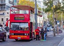 Τουρίστες που ρωτούν το οδηγό λεωφορείου για τις πληροφορίες έξω από την επίσκεψη του λεωφορείου στη Μελβούρνη στοκ εικόνα με δικαίωμα ελεύθερης χρήσης