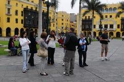 Τουρίστες που στέκονται Plaza de Armas κοντά στην έδρα του περιοδικού Caretas Στοκ Εικόνα