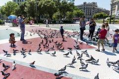 Τουρίστες που ταΐζουν τα περιστέρια μέσα στην Καταλωνία Plaza, Βαρκελώνη, Ισπανία Στοκ Φωτογραφία