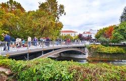 Τουρίστες στη γέφυρα του ποταμού Τρίκαλα Ελλάδα Lithaios στοκ εικόνα
