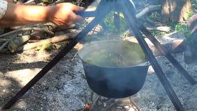 Τουρίστες τροφίμων στρατόπεδων Τρόφιμα στο δοχείο πέρα από την πυρκαγιά Μαγειρευμένος σε μια πυρκαγιά φιλμ μικρού μήκους