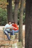 Τουριστικός οδηγός ανάγνωσης ζεύγους στο πάρκο Στοκ φωτογραφία με δικαίωμα ελεύθερης χρήσης