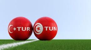 Τουρκία εναντίον Αγώνας ποδοσφαίρου της Τυνησίας - σφαίρες ποδοσφαίρου στα εθνικά χρώματα της Τουρκίας και της Τυνησίας σε ένα γή απεικόνιση αποθεμάτων