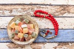 Τουρκικές απολαύσεις στο πιάτο με κόκκινο rosary στον εκλεκτής ποιότητας πίνακα Στοκ Φωτογραφία