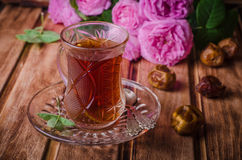 Τουρκικό τσάι σε ένα φλυτζάνι γυαλιού και ξηρά φρούτα ημερομηνιών στο ξύλινο υπόβαθρο Τρόφιμα Ramadan Εκλεκτική εστίαση Στοκ φωτογραφία με δικαίωμα ελεύθερης χρήσης