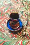 Τουρκικό τσάι στο παραδοσιακά γυαλί τουλιπών και το κουτάλι, ζωηρόχρωμο υπόβαθρο Στοκ Φωτογραφίες