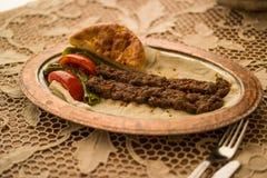 Τουρκικό Adana Kebab σε ένα αγροτικό τραπεζομάντιλο Στοκ εικόνα με δικαίωμα ελεύθερης χρήσης