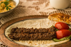 Τουρκικό Adana Kebab σε ένα αγροτικό τραπεζομάντιλο Στοκ Εικόνα