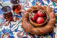 Τουρκικό Bagel Simit με τις ντομάτες τσαγιού και κερασιών στην οθωμανική επιφάνεια σχεδίων Στοκ φωτογραφία με δικαίωμα ελεύθερης χρήσης