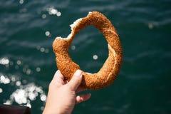 Τουρκικό bagel Snacky σουσάμι στο χέρι του ενάντια στις θάλασσες ενός υποβάθρου Στοκ φωτογραφία με δικαίωμα ελεύθερης χρήσης