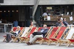 Τους ανθρώπους που διαβάζονται τα βιβλία που κάθονται στους αργοσχόλους κοντά στο εθνικό θέατρο Στοκ φωτογραφία με δικαίωμα ελεύθερης χρήσης