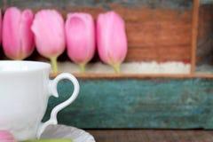 Τουλίπες και φλυτζάνι και πιατάκι με το χρωματισμένο ξύλινο υπόβαθρο Στοκ Φωτογραφίες