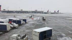 Του δέλτα επίγειο πλήρωμα που εργάζεται σε μια χιονισμένη κεκλιμένη ράμπα aka ποδιών αερολιμένων απόθεμα βίντεο