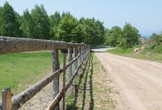 Του χωριού βοοειδές-μάνδρα με τον ξύλινο φράκτη κατά μήκος του δρόμου στοκ φωτογραφίες