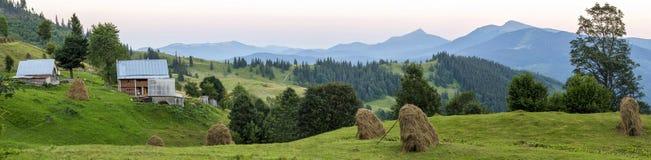 Του χωριού σπίτια στους λόφους με τα πράσινα λιβάδια στη θερινή ημέρα Σπίτι Στοκ Φωτογραφίες