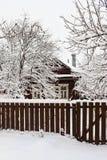 Του χωριού σπίτι κάτω από το χιόνι πίσω από τον ξύλινο φράκτη στοκ εικόνες