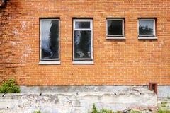 Τούβλινος τοίχος με μερικά παράθυρα Στοκ Εικόνες