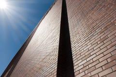 Τούβλινη πρόσοψη τοίχων ενάντια στις ακτίνες μπλε ουρανού και ήλιων Στοκ Φωτογραφία