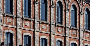 Τούβλινοι τοίχοι και σκοτεινά παράθυρα Στοκ Φωτογραφία