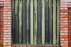 Τούβλινος φράκτης με τις κάθετες ξύλινες σανίδες Στοκ φωτογραφία με δικαίωμα ελεύθερης χρήσης