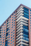 Τούβλινο Condos με τα άσπρα μπαλκόνια και τα μπλε παράθυρα Στοκ Φωτογραφίες