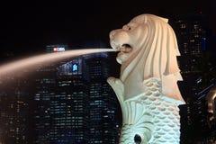 Το άγαλμα Merlion μπροστά από τον ορίζοντα της Σιγκαπούρης τη νύχτα Στοκ φωτογραφίες με δικαίωμα ελεύθερης χρήσης