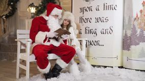 Το άκουσμα μικρών κοριτσιών με προσήλωση ως Santa της διαβάζει μια ιστορία φιλμ μικρού μήκους