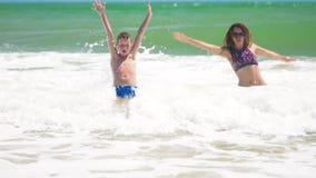 Το άλμα μητέρων και γιων στη θάλασσα στα κύματα, έχει η διασκέδαση φιλμ μικρού μήκους