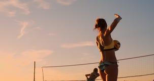 Το άλμα νέων κοριτσιών εξυπηρετεί την πετοσφαίριση στην παραλία, σε αργή κίνηση φιλμ μικρού μήκους