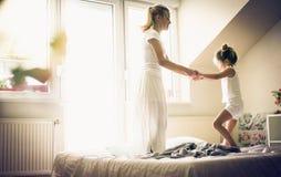 Το άλμα στο κρεβάτι είναι διασκέδαση Μικρό κορίτσι με τη μητέρα της Στοκ εικόνες με δικαίωμα ελεύθερης χρήσης