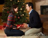 Το άνοιγμα ζεύγους παρουσιάζει μπροστά από το χριστουγεννιάτικο δέντρο Στοκ Φωτογραφίες