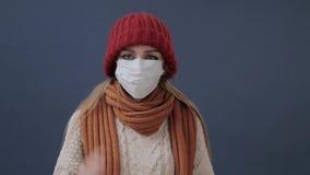 Το άρρωστο κορίτσι βάζει σε μια μάσκα βήχει και λυπημένος απόθεμα βίντεο